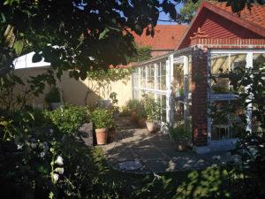 Terrasse i smuk have med drivhus - et lille privat rum.
